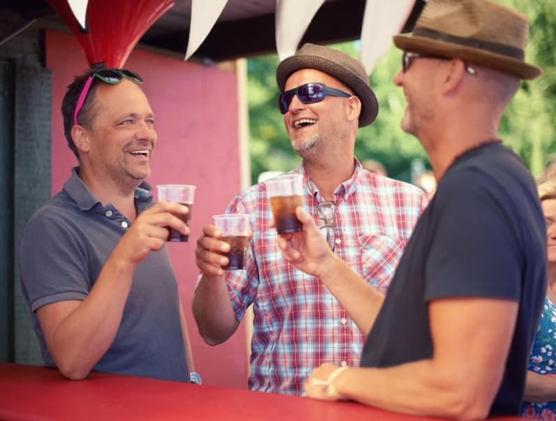 Cropped shot of three male friends drinking at a festival