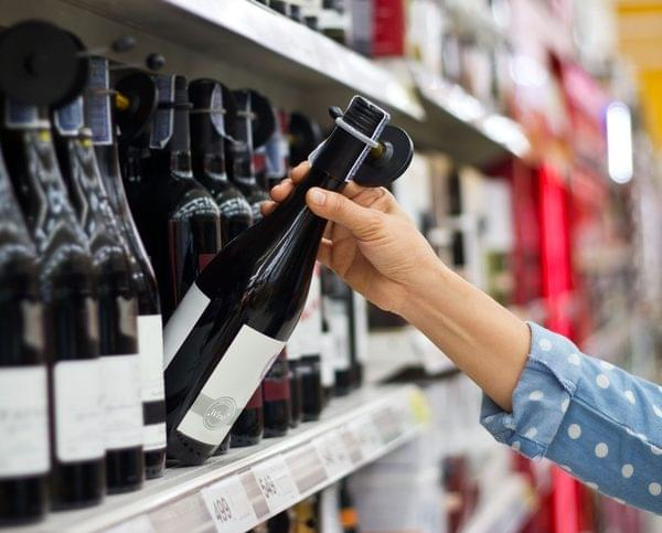 Woman is buying a bottle of wine at the supermarket background